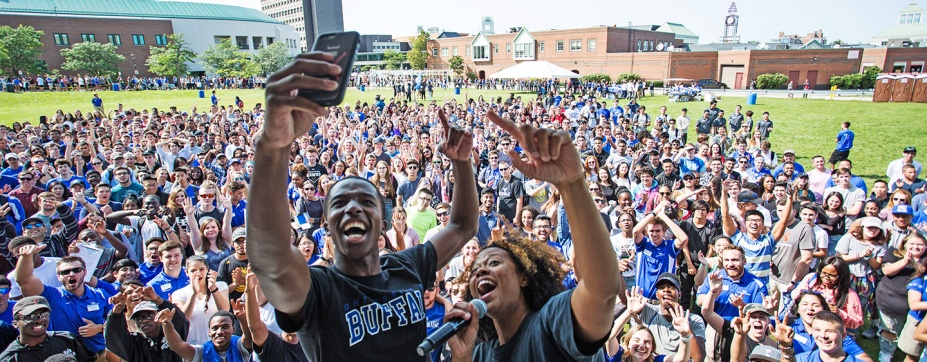 Large group of students outside on campus, many wearing UB blue, and two n front taking a selfie together.