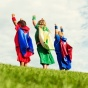 Children in super hero costumes with arms raised energetically.