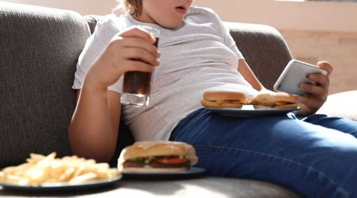 Child eating burgers and drinking soda on a couch while watching a phone.