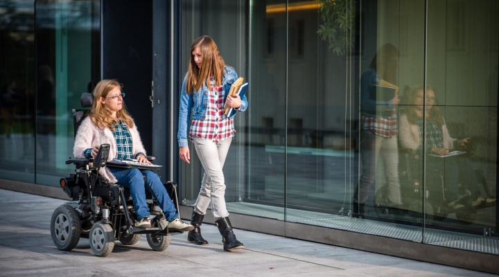 Two students together outside in front of a building, one standing carrying books and one in a wheelchair.