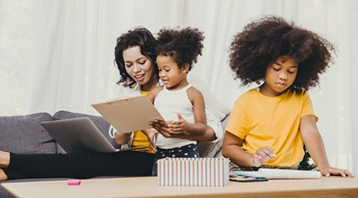 Mom working from home teaching two children.