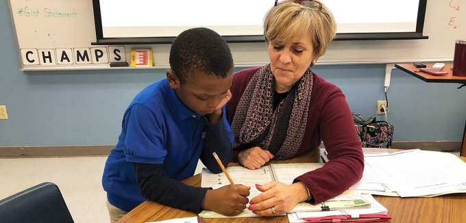 Lynn Shannahan working in a classroom with a student.