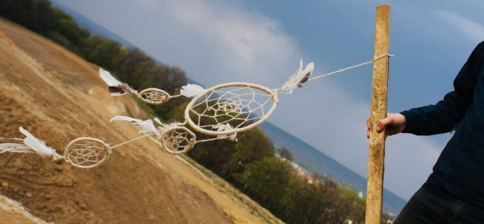 Dream catcher in the wind overlooking a hill in nature.
