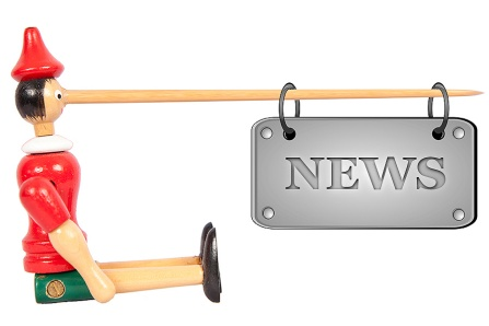 "a Pinocchio doll with a ""news"" sign hanging from a very long wooden nose."