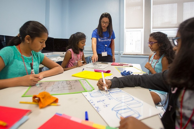 An instructor leads several adolescent female students through an activity during the Summer Math Program.