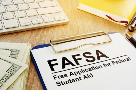 Financial aid concept featuring money, a keyboard and a FAFSA form on a clipboard.