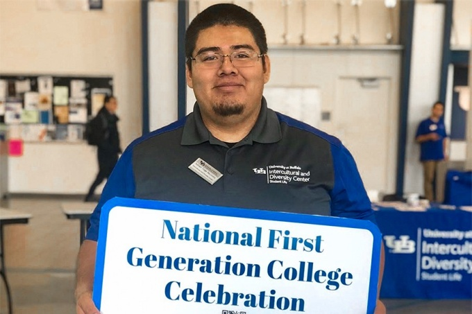"UB graduate Adrian Vega Bautista holding a sign that reads: ""National First Generation College Celebration.""."