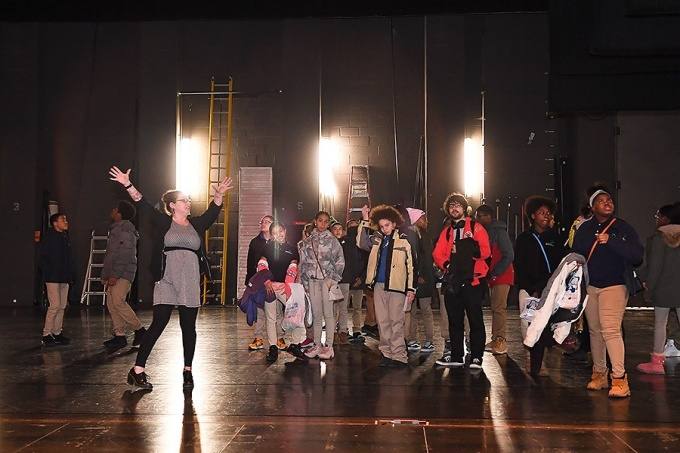 Moriah Bolinsky Hegmann led the eighth graders on a tour through Screening Room, and Mainstage Theater, where she brought them onto the stage.