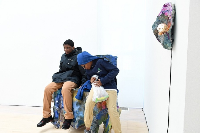 Clinton Peyton and Douglas Peay, visiting the UB Art Gallery, sit on a sculpture by artist Jillian Meyer that invites guests to sit on it.