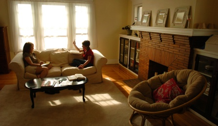 Two female students sit on the couch studying in the living room of a typical Buffalo apartment.